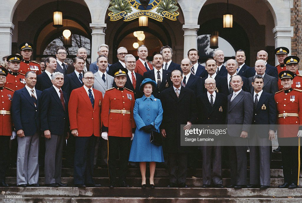 Queen Elizabeth II and Prince Philip pose with members of the Royal Canadian Mounted Police during a tour of Canada, October 1977.