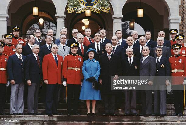 Queen Elizabeth II and Prince Philip pose with members of the Royal Canadian Mounted Police during a tour of Canada October 1977