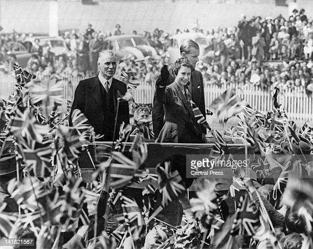 Queen Elizabeth II and Prince Philip surrounded by a mass of flagwaving children during a children's picnic at Forbury Park Racecourse Dunedin New...