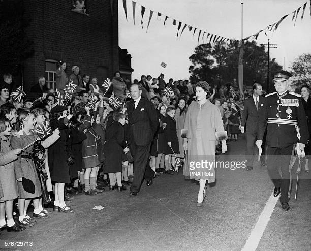 Queen Elizabeth II and Prince Philip walk past crowds of cheering schoolchildren in Brentwood Essex 30th October 1957 The Queen is there to perform...
