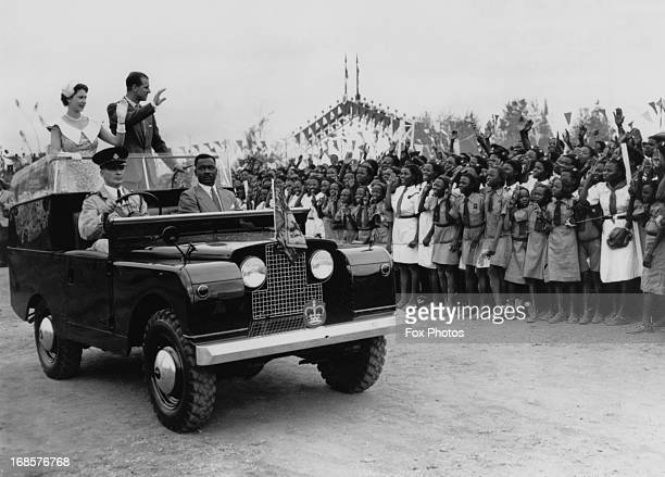 Queen Elizabeth II and Prince Philip wave from an open Land Rover to a crowd of schoolchildren at a rally held at a racecourse in Ibadan Nigeria 15th...
