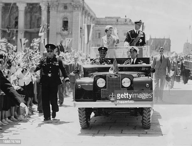 Queen Elizabeth II and Prince Philip wave from an open Land Rover to a crowd in Tobruk during an official visit to Libya May 1954