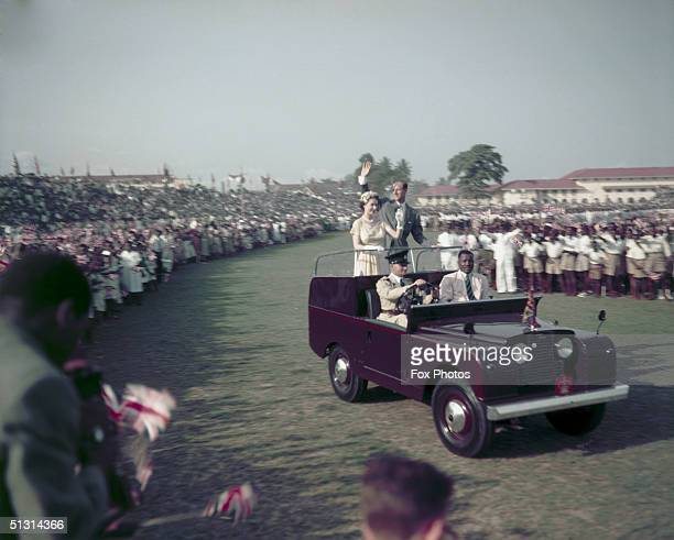Queen Elizabeth II and Prince Philip waving from a Land Rover at a youth rally on the racecourse at Lagos Nigeria 10th February 1956