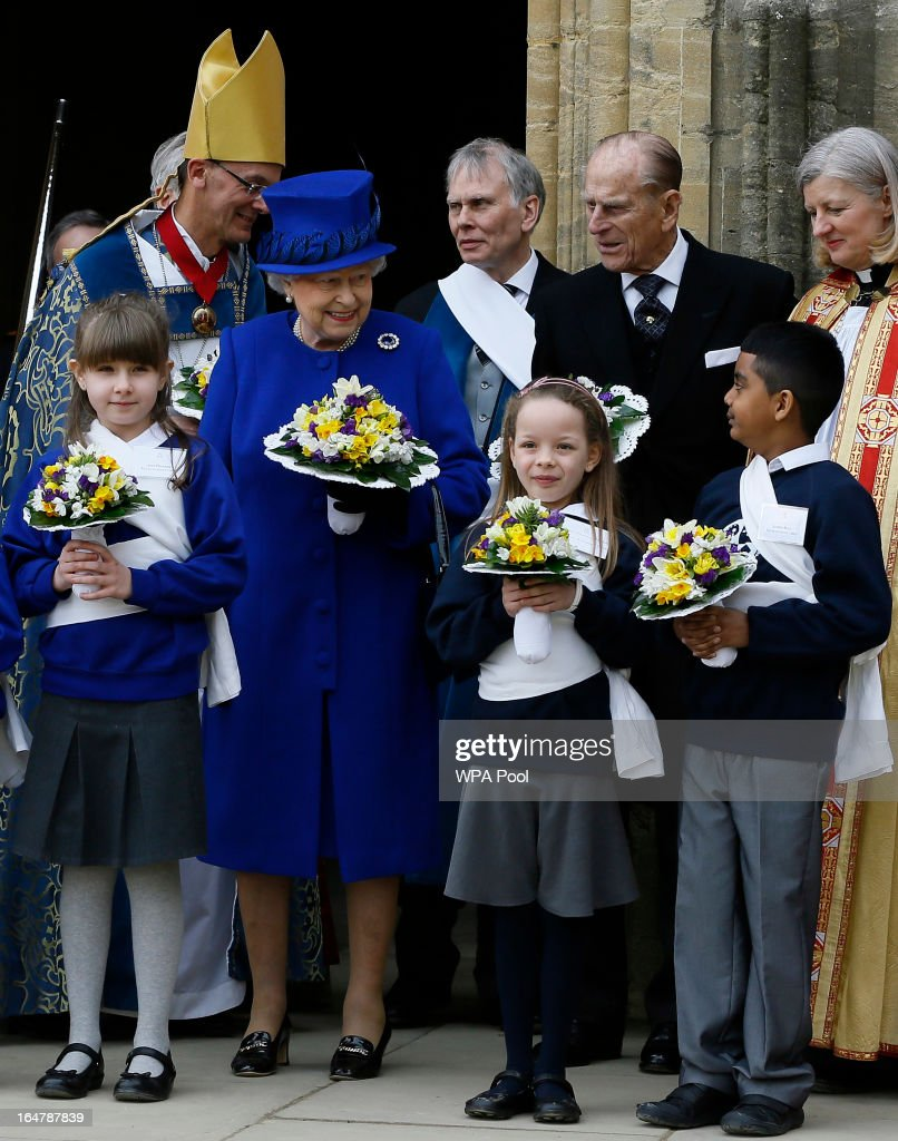 Queen Elizabeth II and Prince Phillip, Duke of Edinburgh pose with children after attending the Maundy service, at Christ Church Cathedral on March 28, 2013 in Oxford, England. The Maundy money was today distributed by the Queen to 87 women and 87 men, who each received two purses, one red and one white. A 5 GBP coin and 50 pence coin commemorating the 60th anniversary of The Queen's Coronation in the red purse. The white purse contains the uniquely minted Maundy Money. This takes the form of silver one, two, three and four penny pieces, the sum of which equals the number of years the Monarch's age.