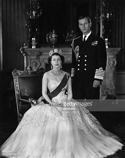 Queen Elizabeth II and Prince Phillip She is seated and wearing a crown he is standing in uniform Undated photograph