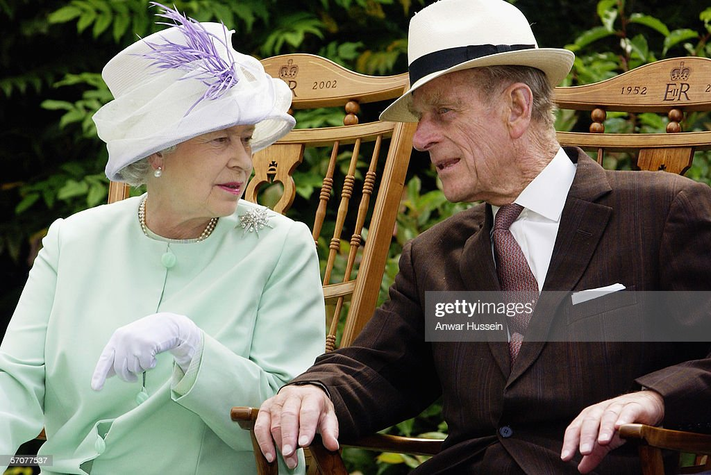 Queen Elizabeth II and Prince Phillip the Duke of Edinburgh chat while seated during a musical performance in the Abbey Gardens, Bury St Edmunds during her Golden Jubilee visit to Suffolk on the 18th of July 2002.