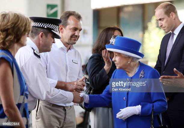 Queen Elizabeth II and Prince William Duke of Cambridge greet members of emergency services at the scene of the Grenfell Tower fire on June 16 2017...