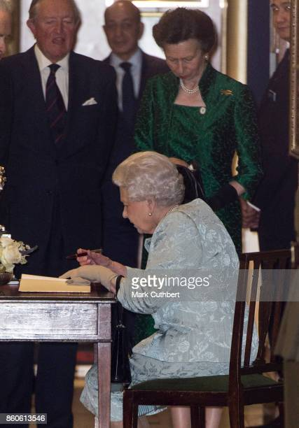 Queen Elizabeth II and Princess Anne Princess Royal sign the visitors book after a reception to mark the Centenary of the Women's Royal Navy Service...