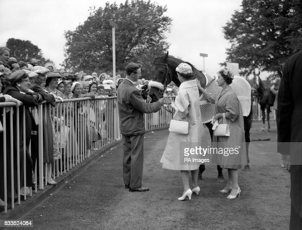 Queen Elizabeth II and Princess Margaret make a fuss of the Queen's colt Restoration in the unsaddling enclosure after he had won the King Edward VII...