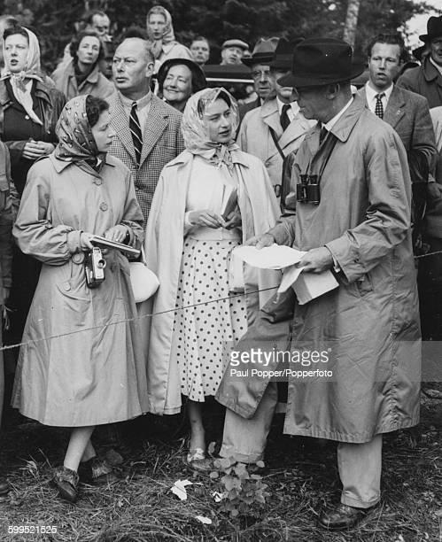 Queen Elizabeth II and Princess Margaret talking to King Gustaf VI Adolf of Sweden with Prince Henry Duke of Gloucester standing behind Her Majesty...