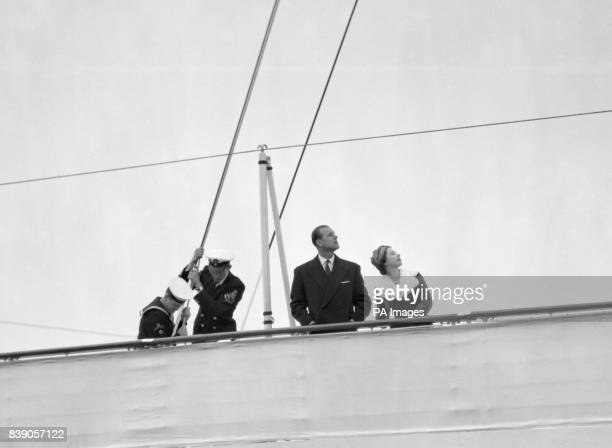 Queen Elizabeth II and the Duke of Edinburgh look up as the Royal Standard is broken at the mainmast of the Royal Yacht Britannia before leaving on...
