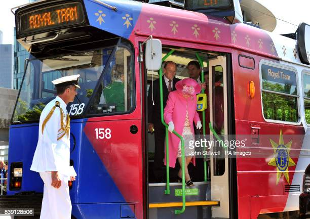 Queen Elizabeth II and the Duke of Edinburgh prepare to step off an electric Tram after a short journey through the Melbourne city centre past huge...