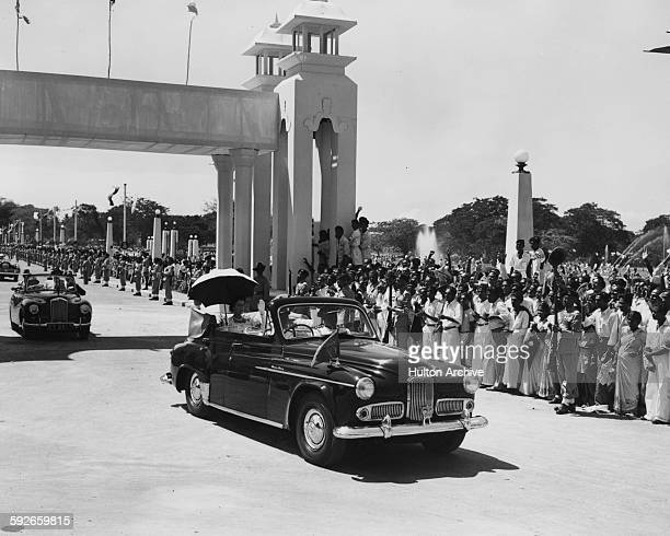 Queen Elizabeth II and the Duke of Edinburgh riding in the back of an open car under an umbrella driving through the crowded streets of Colombo...