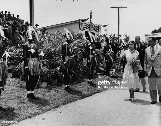 Queen Elizabeth II and the Duke of Edinburgh walk past some of the 21 native representatives who were chosen by their fellow countrymen of New Guinea...