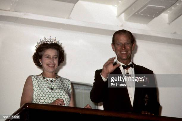 Queen Elizabeth II and the Duke of Edinburgh wave to the crowds from the Royal Yacht Britannia as it leaves Tortola in the Virgin Islands during the...