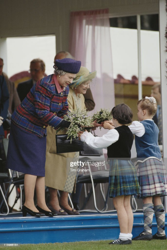 Queen Elizabeth II and the Queen Mother (1900-2002) accepting posies of heather from two young children in Highland dress at the Braemar Gathering, an annual Highland games event in Braemar, Aberdeenshire, Scotland, Great Britain, 3 September 1994.
