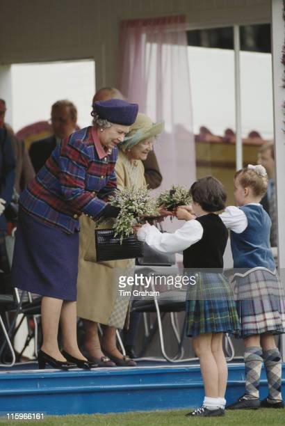 Queen Elizabeth II and the Queen Mother accepting posies of heather from two young children in Highland dress at the Braemar Gathering an annual...