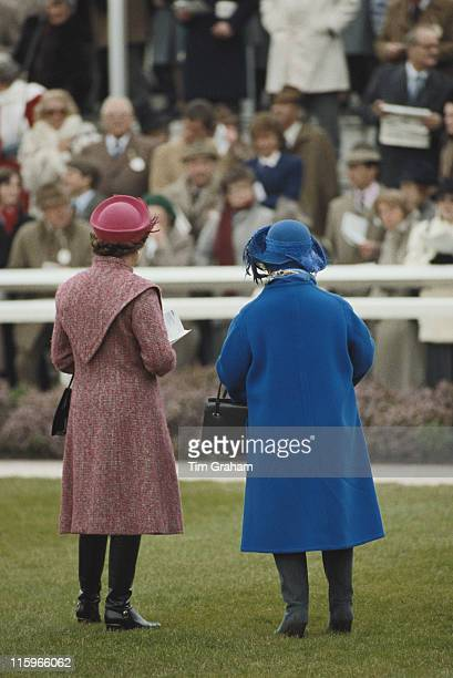 Queen Elizabeth II and the Queen Mother with their backs to the camera watching the racing at Sandown Park racecourse in Esher Surrey England Great...