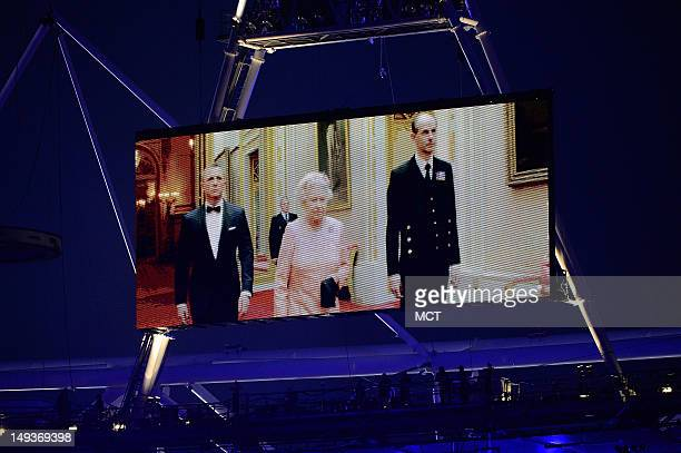 Queen Elizabeth II appears on a large video screen accompanied by Prince Philip right and actor Daniel Craig during the Opening Ceremony for the 2012...