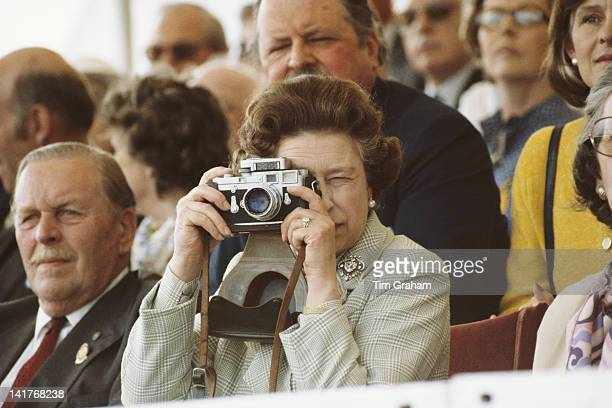 KINGDOM Queen Elizabeth II at The Windsor Horse Show 16th May 1982 She is taking pictures of her husband with her Leica M3 camera She is wearing her...