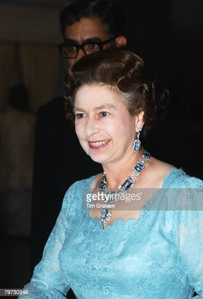 Queen Elizabeth II attends a banquet in India wearing a suite of aquamarine and diamond jewels that was a Coronation present from the President and...