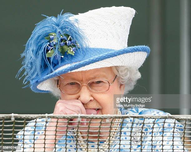 Queen Elizabeth II bites her nails whilst watching the racing from the balcony of the Royal Box as she attends Derby Day during the Investec Derby...