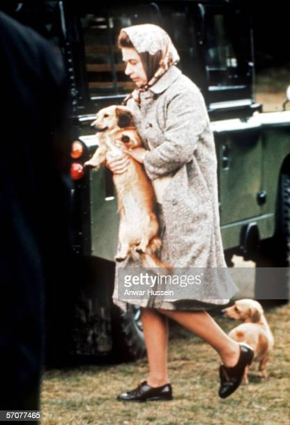Queen Elizabeth II carries one of her pet dogs at Windsor Great ParkEngland