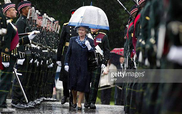 Queen Elizabeth II carrying an umbrella to protect her from the torrential rain inspects members of the 1st Battalion The Royal Scots 01 July 2003 at...