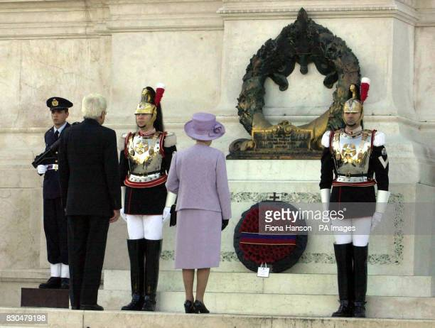 Queen Elizabeth II centre and Rome's Minister of Defence Sergio Mattarella stand to attention after a wreath is laid on their behalf by the...