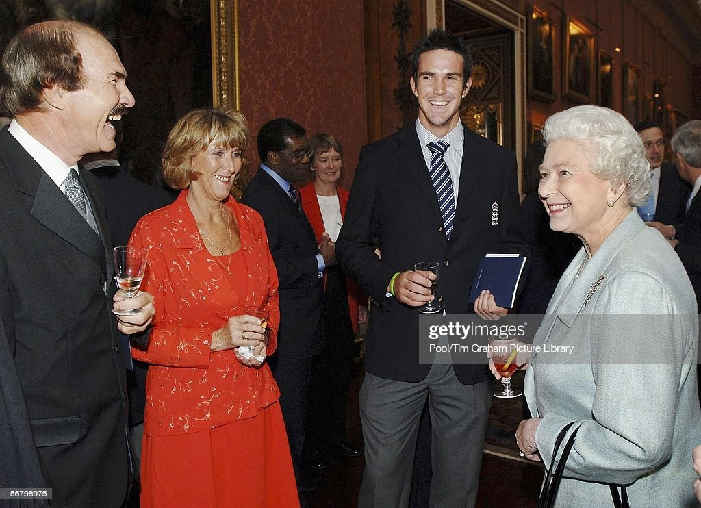 Queen Elizabeth II chats with Ashes winning England cricketer <a gi-track='captionPersonalityLinkClicked' href=/galleries/search?phrase=Kevin+Pietersen+-+Cricketspieler&family=editorial&specificpeople=202001 ng-click='$event.stopPropagation()'>Kevin Pietersen</a> (C) and his mother Penny and father Jannie, during a reception following the Investiture ceremony at Buckingham Palace on February 9, 2006 in London.