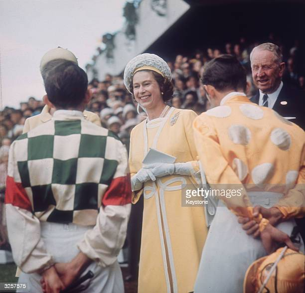 Queen Elizabeth II chats with jockeys Ron Quinton and Hilton Cope before the Queen Elizabeth Stakes at Randwick race course near Sydney during her...