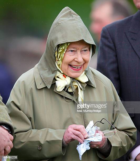 Queen Elizabeth II cleans her glasses as she watches one of her horses compete in the Highland class on day 3 of the Royal Windsor Horse Show on May...