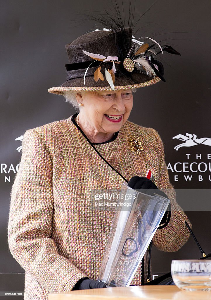 Queen Elizabeth II collects her trophy after her horse 'Sign Manual' won The Dreweatts Handicap Stakes at Newbury Racecourse on April 19, 2013 in Newbury, England.