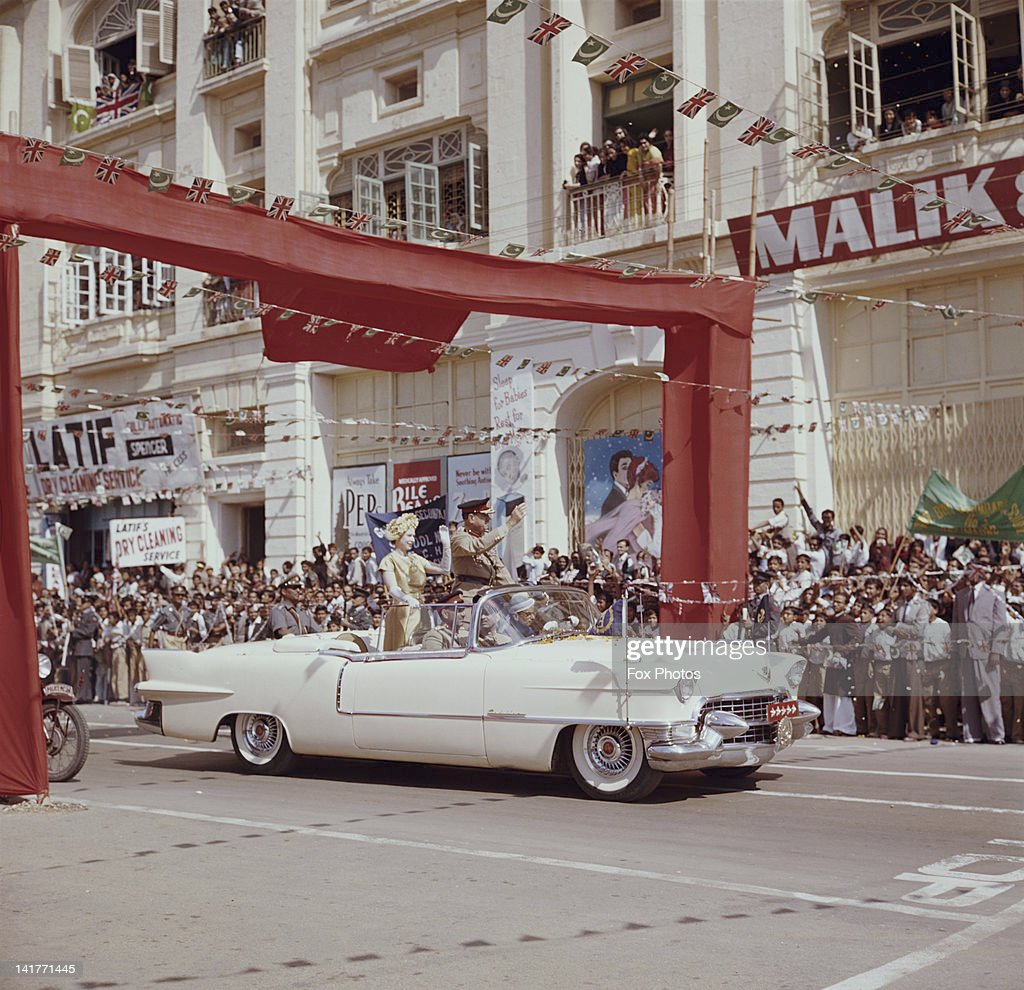 Queen Elizabeth II drives through Karachi in a white Cadillac, at the start of her visit to Pakistan, 1st February 1961. She is accompanied by Pakistani President Ayub Khan (1907 - 1974).