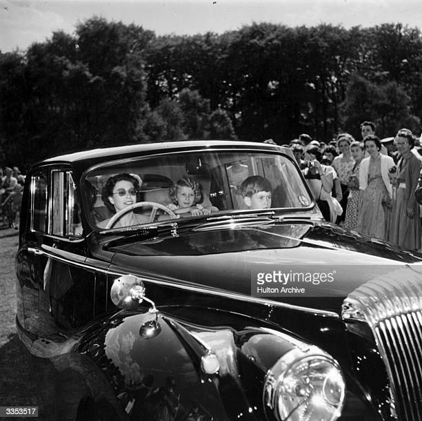 Queen Elizabeth II driving a Daimler with Prince Charles and Princess Anne as passengers