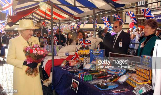 Queen Elizabeth II examines the stall of Raymond Nathan and Janet Gardner during the tour of the market square in Enfield Town centre London During...