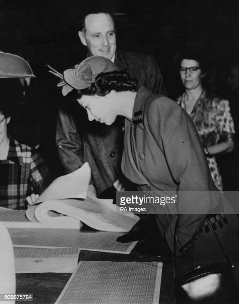Queen Elizabeth II examining the first stamps of her reign during her tour of the stamp printing works of Messrs Harrison and Sons Ltd at High...