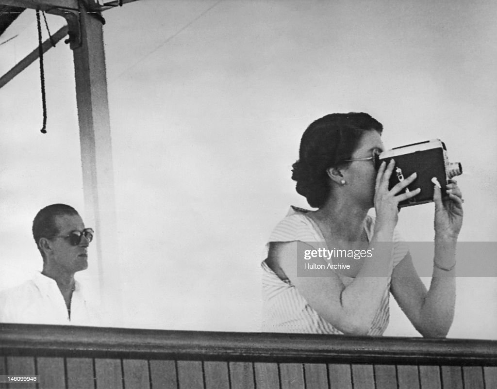 Queen Elizabeth II filming the arrival of the escort ship HMNZS Black Prince, while in the South Pacific en route to Fiji, aboard the SS Gothic during the coronation world tour, 11th December 1953. On the left is Prince Philip.