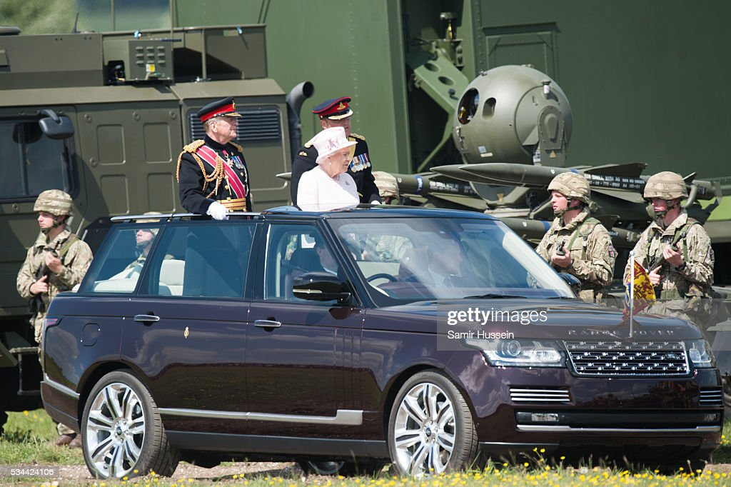 Queen Elizabeth II, General-Captain of the Royal Regiment of Artillery, rides in an open top Range Rover as she overseas a Royal Review on the occasion of their Tercentenary at Knighton Down on May 26, 2016 in Lark Hill, England.