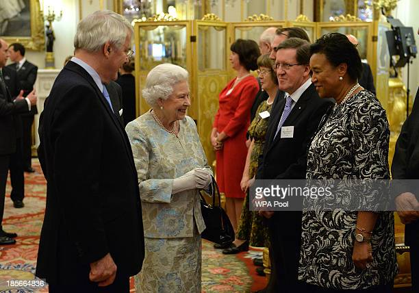 Queen Elizabeth II greets Baroness Scotland of Asthal as Sir John Major looks on during a reception for The Queen Elizabeth Diamond Jubilee Trust at...