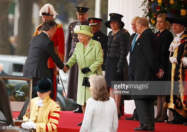 Queen Elizabeth II greets Colombia's President Juan Manuel Santos as Prince Philip looks on at a ceremonial welcome for Colombia's President Juan...