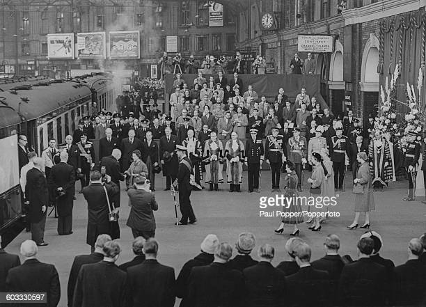 Queen Elizabeth II greets Theodor Heuss President of the Federal Republic of Germany as the Duke of Edinburgh looks on in front of a gathered crowd...