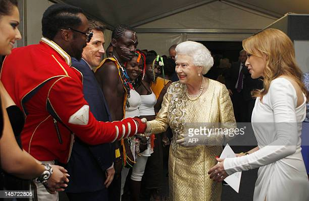 Queen Elizabeth II greets US singersongwriter william and Australian singer Kylie Minogue backstage during the Diamond Jubilee Concert outside...
