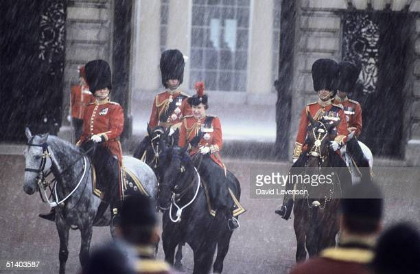 Queen Elizabeth II grimacing in driving rain as she takes the salute outside Buckingham Palace at the Trooping the Colour ceremony in London on June...
