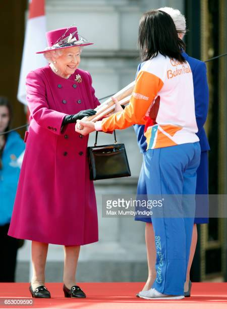Queen Elizabeth II hands former track cyclist Anna Meares of Australia The Queen's Baton during the launch of The Queen's Baton Relay for the XXI...