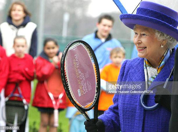 Queen Elizabeth II holds a tennis racquet signed by the British Davis Cup team which was presented to her during her visit to the new National Tennis...