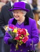 Queen Elizabeth II holds bunches of flowers given to her by members of the public during a walkabout after attending Sunday service at the church of...