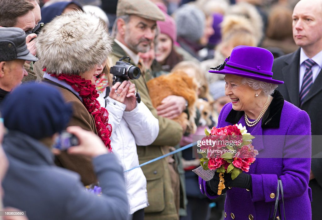 Queen Elizabeth II holds bunches of flowers given to her by members of the public during a walkabout after attending Sunday service at the church of St Peter and St Paul in West Newton on February 03, 2013 near King's Lynn, England.