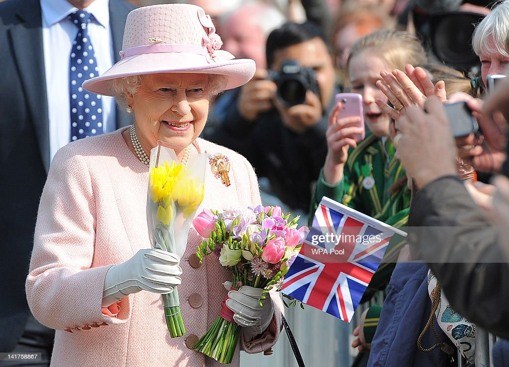 Queen <a gi-track='captionPersonalityLinkClicked' href=/galleries/search?phrase=Elizabeth+II&family=editorial&specificpeople=67226 ng-click='$event.stopPropagation()'>Elizabeth II</a> holds flowers as she is greeted by well-wishers outside Media City in Salford, on March 23, 2012 in Greater Manchester, north-west England. The Queen and her husband, Prince Philip, the Duke of Edinburgh visited Manchester where she officially opened hospitals, toured the new BBC building at MetroCity and officially started a Sport Relief Mile fun run.