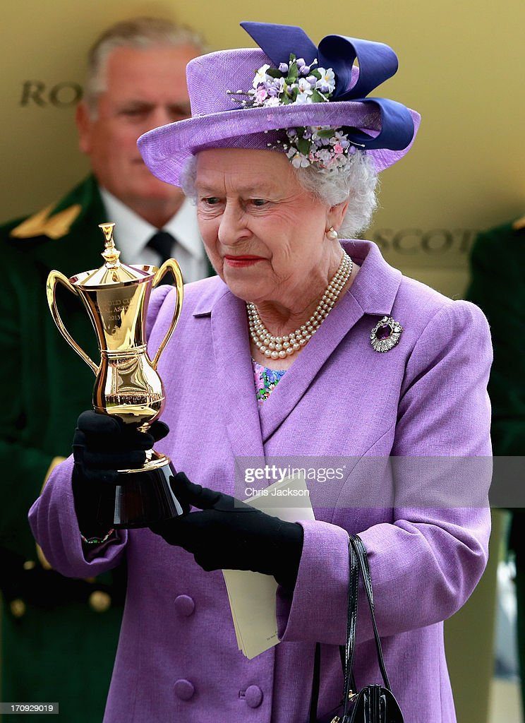 Queen Elizabeth II holds the Gold Cup after Ryan Moore riding Estimate won The Gold Cup during Ladies' Day on day three of Royal Ascot at Ascot Racecourse on June 20, 2013 in Ascot, England.
